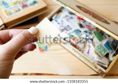 Collection of postage stamps of different countries lying on a wooden table. Hand holds a blank postage stamp #1108183355