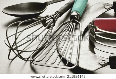 Collection of retro, vintage kitchen utensils. Black and white with original color in wooden handles.