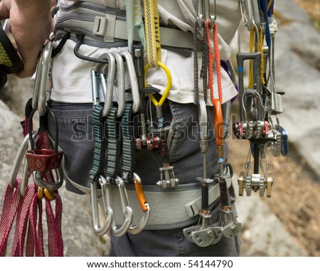 Collection of rock climbing gear attached to a climber\'s harness