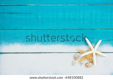 Collection Of Seashells And Starfish In Sand Border On Antique Rustic Teal Blue Wood Background