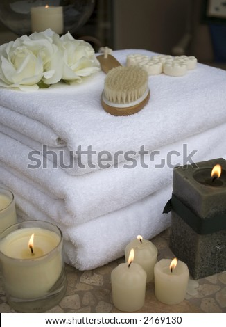 collection of towels and candles and spa accessories at spa with waterfall