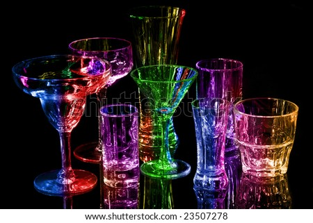 Collection of various bar glasses isolated on black with reflection, multi-colored