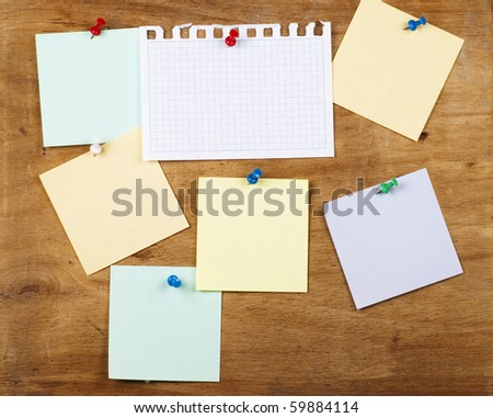 collection of various note papers on an old wooden board