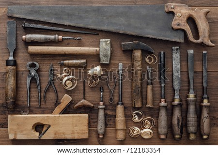 Collection of vintage carpentry tools on an old workbench: woodworking, craftsmanship and handwork concept, flat lay