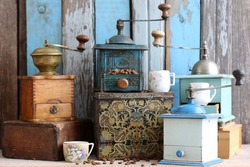 Collection of Vintage Old Aged Weathered Rusty Mechanical Metal Coffee Grinder, Houseware, beans on Tin Box, Kitchen Decor, antique china cup on wooden blue and grey color background, rural style