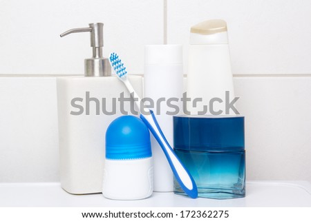 collection of white and blue cosmetic bottles over tiled wall in bathroom