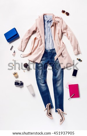 Shutterstock collection of women's clothing and accessories. Overhead of essentials young woman. Outfit of casual and elegant woman, jeans, high heels shoes, pink coat, handbag, notebook, telephone, sunglasses.