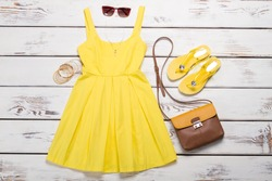 Collection of women's summer clothes. Yellow bright dress with accessories on wooden background.