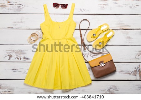 Collection of women\'s summer clothes. Yellow bright dress with accessories on wooden background.