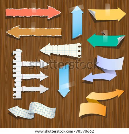 Collection paper arrows on wooden background.Raster version