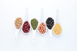 Collection set of beans, legumes, peas, lentils on ceramic spoons isolated on white background.