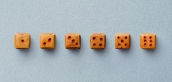 Collection wooden dices organized in a line over blue background, above view