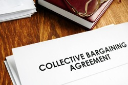 Collective bargaining agreement and note pad with glasses.