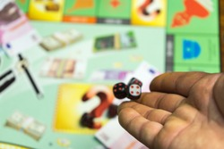 Collective Board game. Man throws game cubes on the playing field.