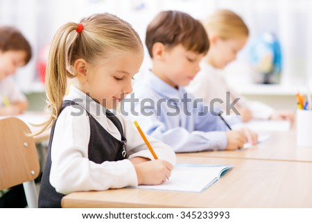 Collective work. Little pupils are all busy writing in their copybooks.