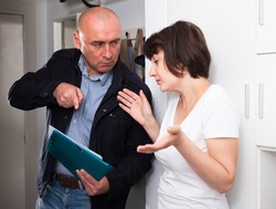 Collector is trying to get the arrears from woman at home door. High quality photo