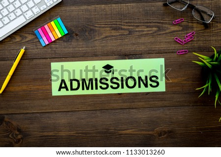 College admission concept. Word admissions with graduation cap sign on dark wooden student desk with computer top view copy space