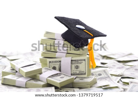 College Admissions Scandal: Mortarboard on a pile of money representing the high cost of education, Student Loans and bribery. Bills are Stage Money.