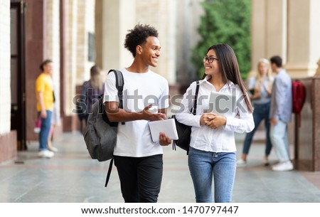 College friends walking in campus and talking, having break after classes