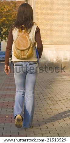 College girl with backpack walking near the university building.