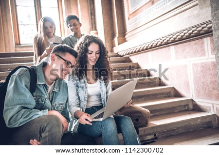 College life.Group of students using a laptop while sitting on stairs in university.