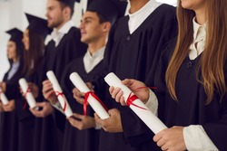 College or university students in black gowns holding traditional diploma scrolls at graduation ceremony. Happy graduates with certificates in hands celebrating milestone life event of getting degree