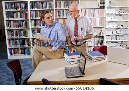 College professor with male student conversing in library