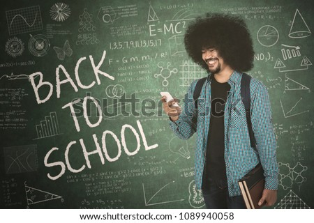 College student looking at smartphone while standing with back to school text and doodle on chalkboard