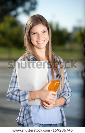College student outdoor with drink and notebook in hand