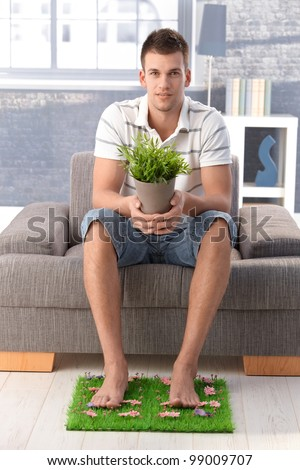 College student sitting in living room at home, desiring for nature, holding potted plant, resting legs on artificial grass.