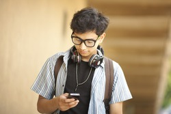 College student standing with mobile phone horizontal image