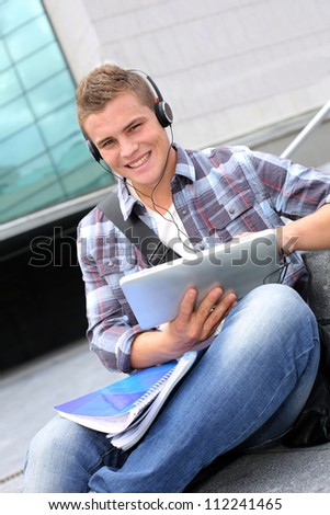 College student using digital tablet and headphones