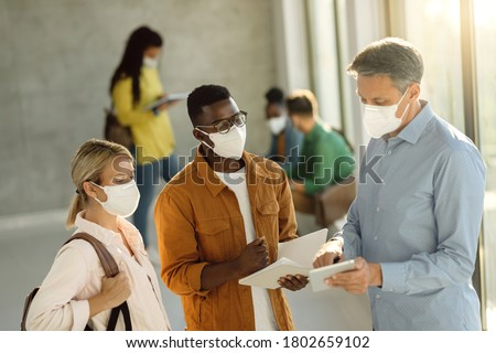 College students and their teacher wearing protective face masks while using touchpad in a hallway. Focus is on African American student.