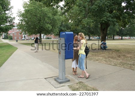College students on campus.  Girls yelling into payphone.