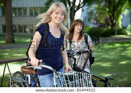 College students standing with bicycle on college campus lawn - stock photo