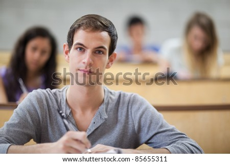 College students taking notes in an amphitheater with the camera focus on the foreground - stock photo