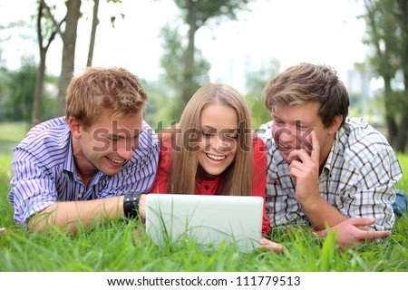 College students using laptop on campus lawn