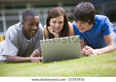 College students using laptop on campus lawn,