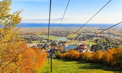 Collingwood area,Blue Mountain village, resort, Ontario, Canada,Oct.17,2020, nice inviting natural landscape view from the mountain with open air gondola going down on sunny autumn day and blue sky