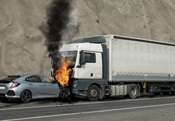 Collision between a car and a truck transporting goods. Accident followed by fire. The car caught fire after the frontal impact.