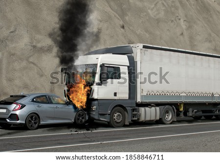 Photo of  Collision between a car and a truck transporting goods. Accident followed by fire. The car caught fire after the frontal impact.