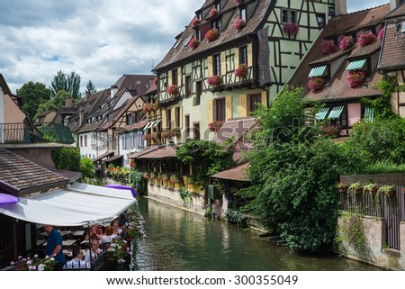 COLMAR, FRANCE - JUNE, 20: Colorful traditional french houses and a small restaurant terrace on the side of river Lauch in Petite Venice, Colmar, France on June, 20, 2015