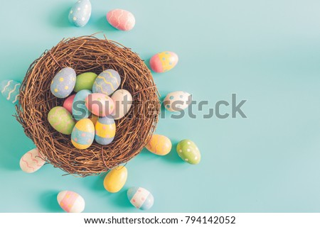 Coloeful easter eggs in nest on pastel color background with space.
