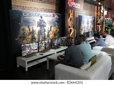 COLOGNE - AUGUST 16: Videogamers playing Gears of War 3 at GamesCom 2011, the most important European video games Expo August 16, 2011 in Cologne, DE