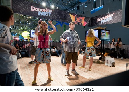 COLOGNE - AUGUST 20: Young videogamers playing with PlayStation Move at GamesCom 2011, the most important European video games Expo August 20, 2011 in Cologne, DE - stock photo