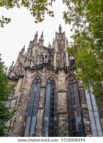 Cologne Cathedral or Cathedral Church of Saint Peter, exterior partial view behind tree branches #1518408494