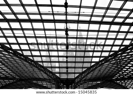 Cologne cathedral through transparent roof of railway station black and white