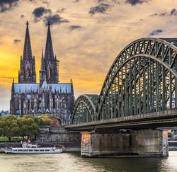Cologne, Germany at the cathedral and bridge over the Rhine River.