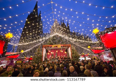 COLOGNE, GERMANY - DECEMBER 23: People at a Christmas market on December 23, 2011 in Cologne, Germany. The history of these markets goes back to the Late Middle Ages in the German part of Europe.
