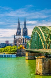 Cologne historical city centre with Cologne Cathedral Roman Catholic Church Saint Peter gothic style building, Hohenzollern Bridge across Rhine river, vertical view, North Rhine-Westphalia, Germany